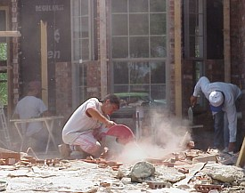 A workman is cutting bricks to use around the windows.