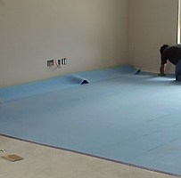 A worker cuts and installs carpet cushion, a layer of padding underneath the carpet.