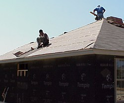 The workers are starting to install  the roofing shingles.
