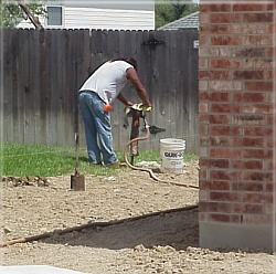 On this property, the worker has to dig through rock to install many of the fence posts.