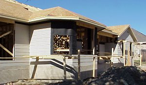 "A view of the back of the house on February 14, 1999.  This picture shows the initial ""hardi plank"" siding that has been installed and also the roof decking."