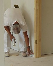 This picture shows a workman applying caulk to seal cracks and holes, creating a smooth surface for painting.