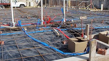 Installation of the copper plumbing lines under the rebar above the plastic.