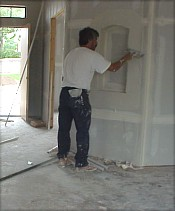 A workman taping and floating the walls...