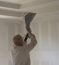 A workman is spraying texture on the interior walls.