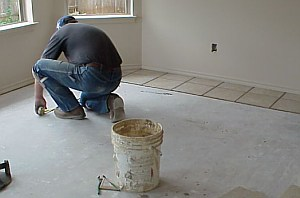 A workman is measuring the floor,