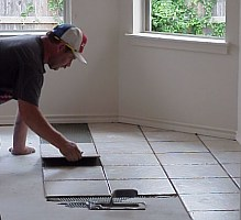 In this picture, the worker is setting the tile.